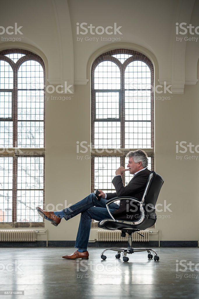 Mature businessman sitting on office chair stock photo