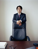 Mature businessman standing behind chair in office, portrait