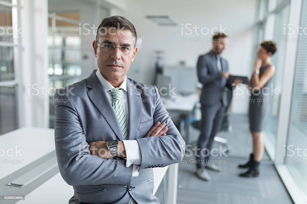 Mature businessman standing with arms crossed in the office. stock photo