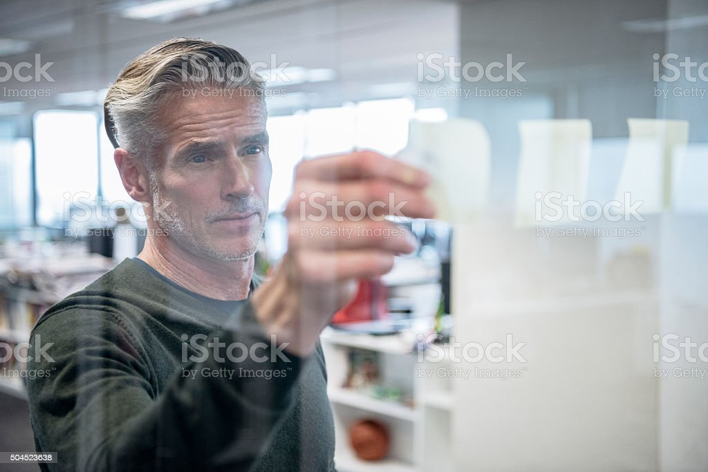 Mature businessman sticking notes on to glass, serious expression stock photo