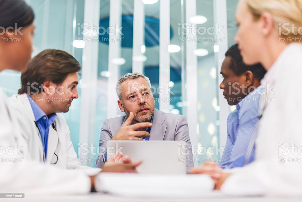 Mature businessman talking on a meeting with doctors. stock photo