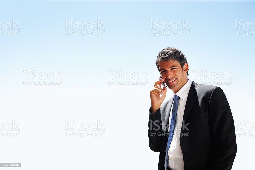 Mature businessman talking on cellphone and looking away royalty-free stock photo