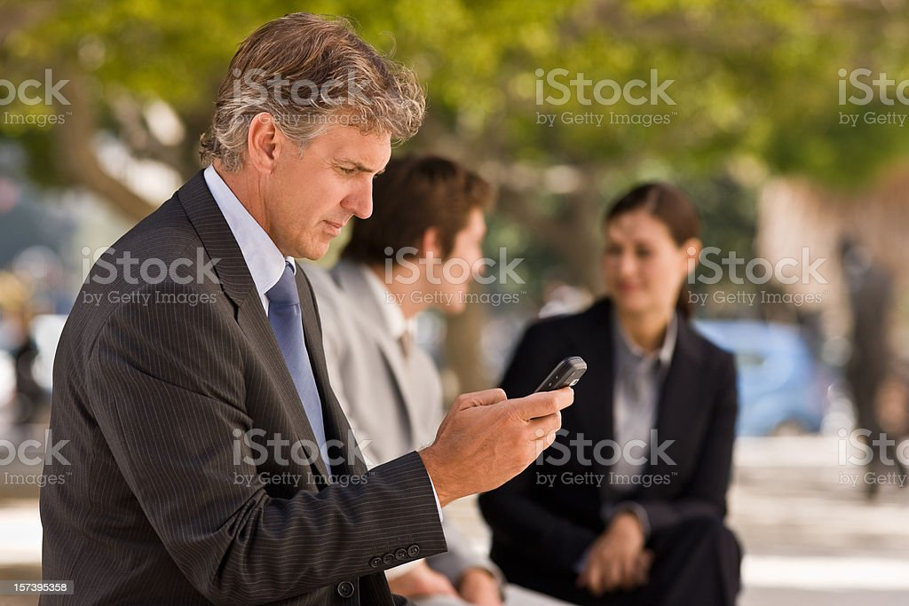 Mature businessman text messaging on mobile phone royalty-free stock photo