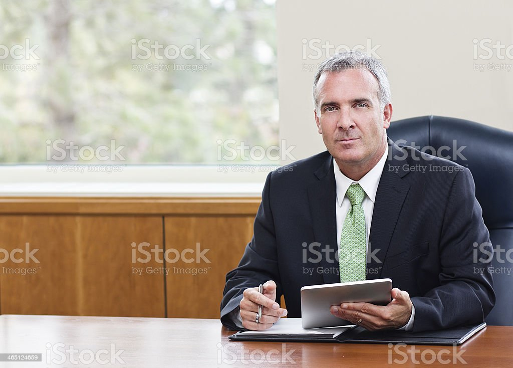 Mature businessman using a tablet computer at a desk  stock photo