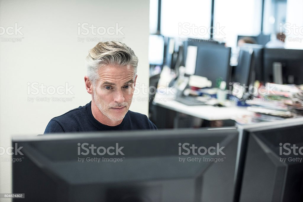 Mature businessman using computer in modern office stock photo