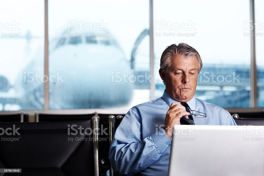 Mature businessman using laptop with aeroplane in the background royalty-free stock photo