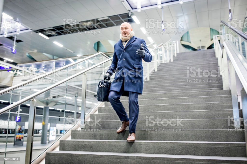 Mature businessman walking down the stairs at metro station stock photo