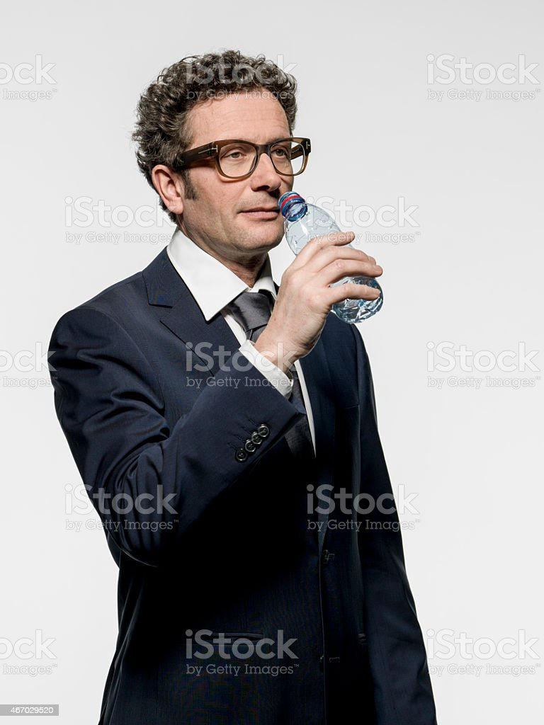 mature businessman water drinking from a PET bottle stock photo