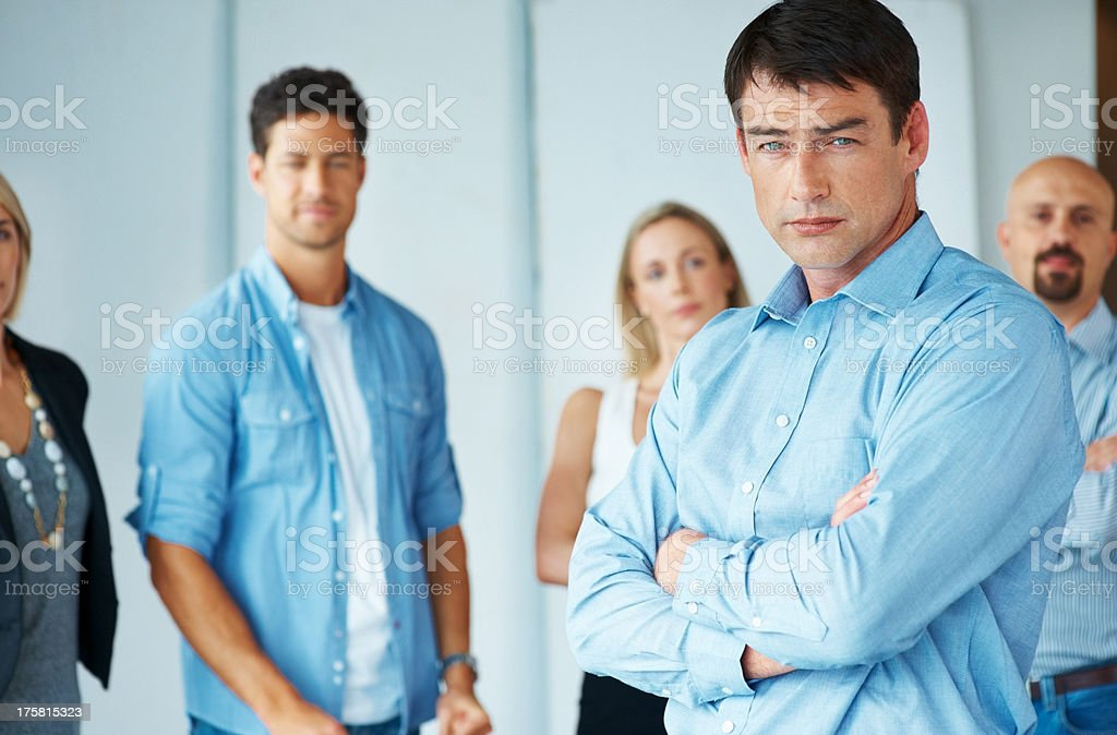 Mature businessman with a group of people at the back stock photo