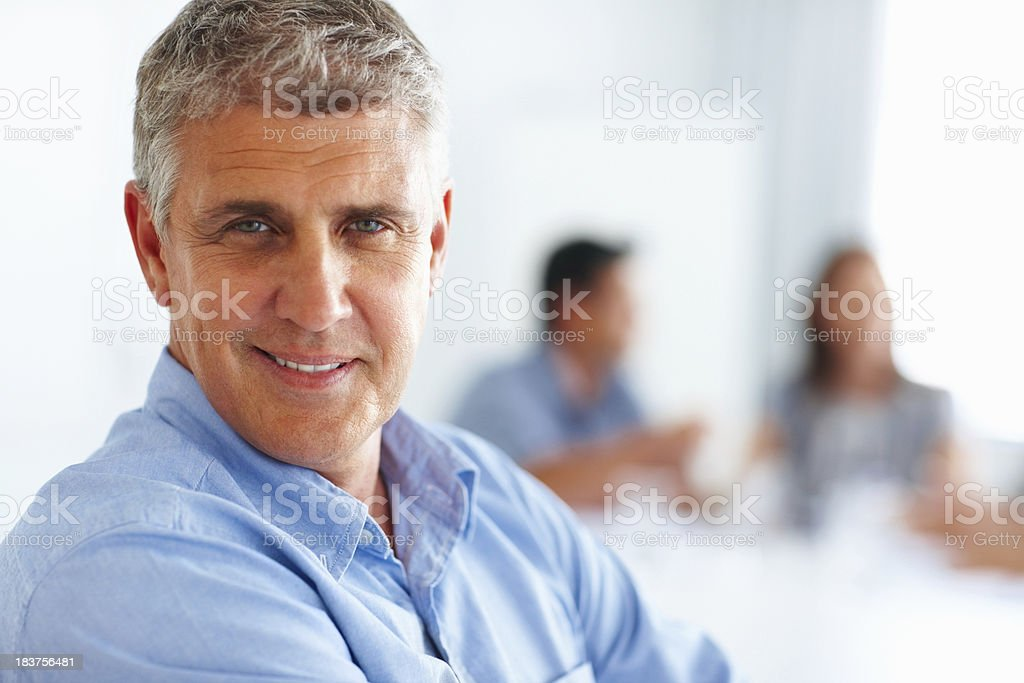 Mature businessman with colleagues in background royalty-free stock photo