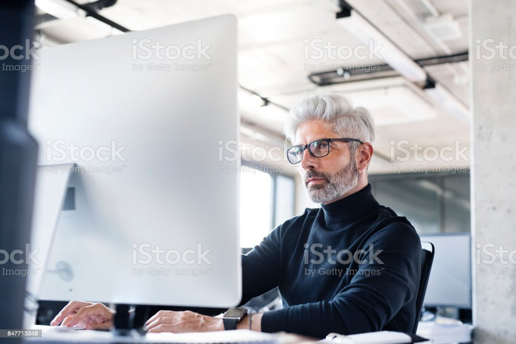 Mature businessman with computer in the office. stock photo