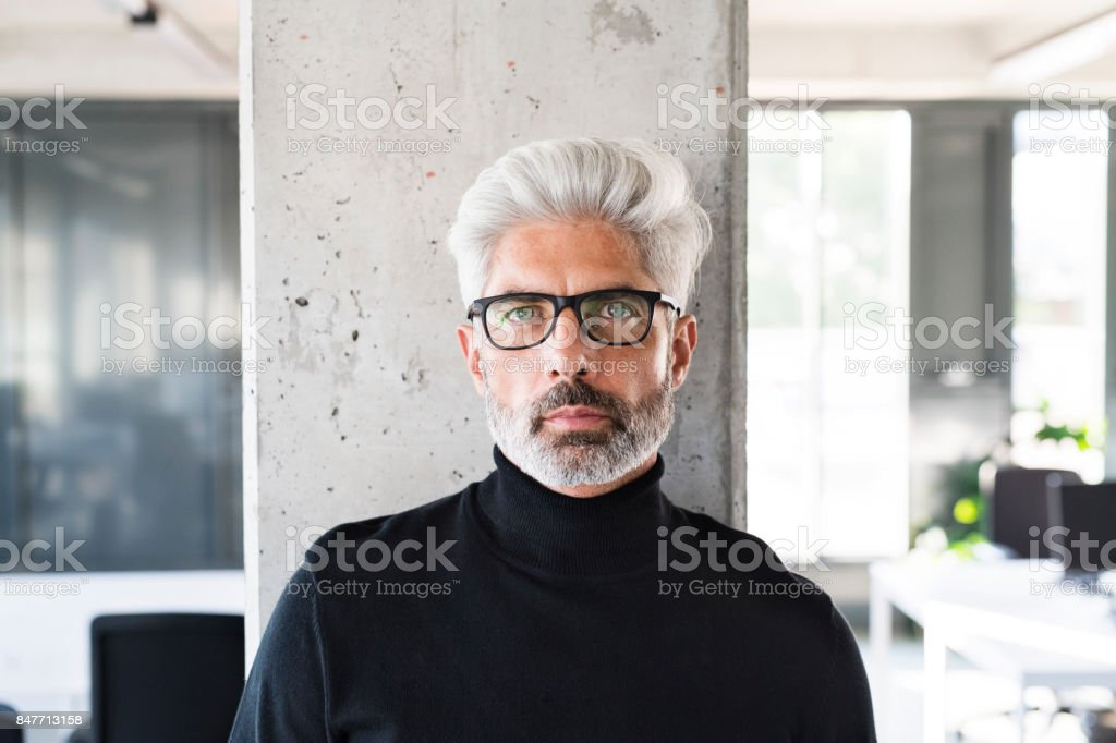 Mature businessman with gray hair in the office. stock photo
