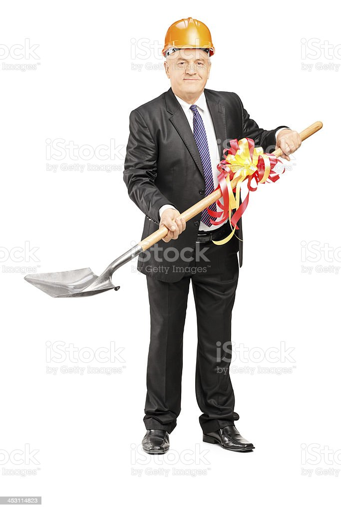 Mature businessman with helmet holding a shovel stock photo