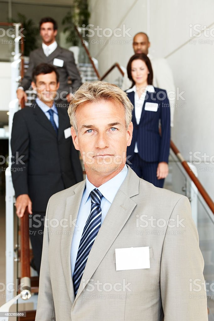 Mature businessman with his colleagues in background royalty-free stock photo