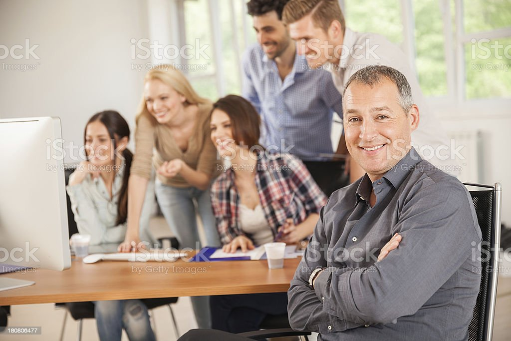 Mature businessman with his young colleagues royalty-free stock photo