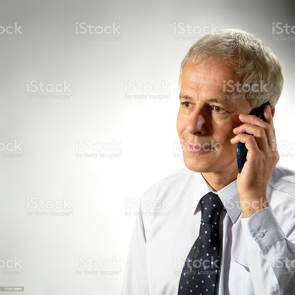 Mature businessman with mobile is talking on the phone, studio royalty-free stock photo
