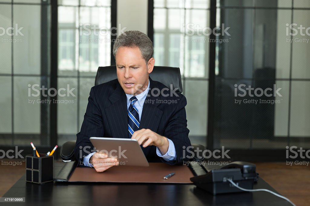 Mature Businessman Working On Digital Tablet royalty-free stock photo