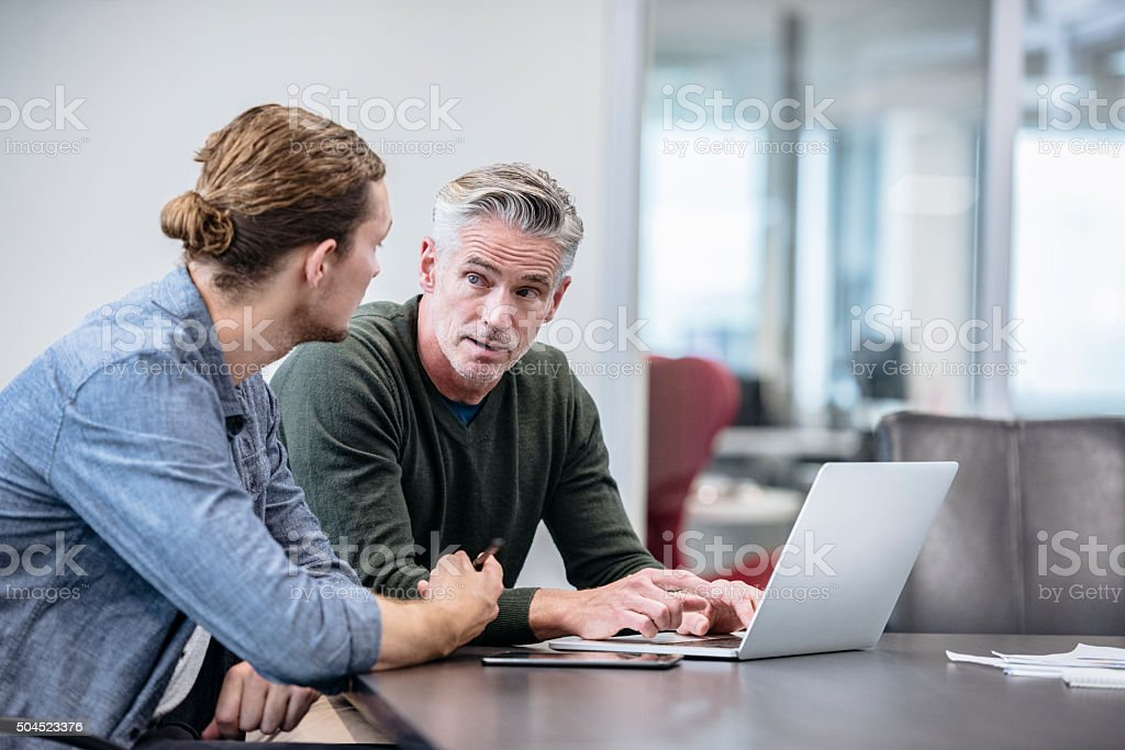 Mature businessmen explaining to colleague using laptop stock photo