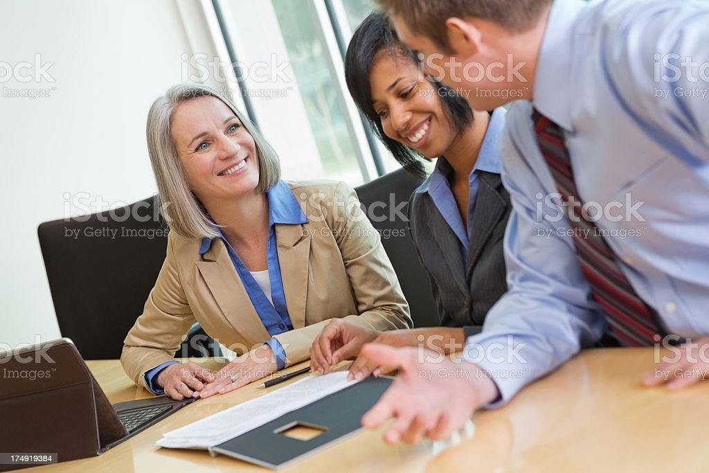 Mature businesswoman discussing ideas with colleagues in business meeting royalty-free stock photo