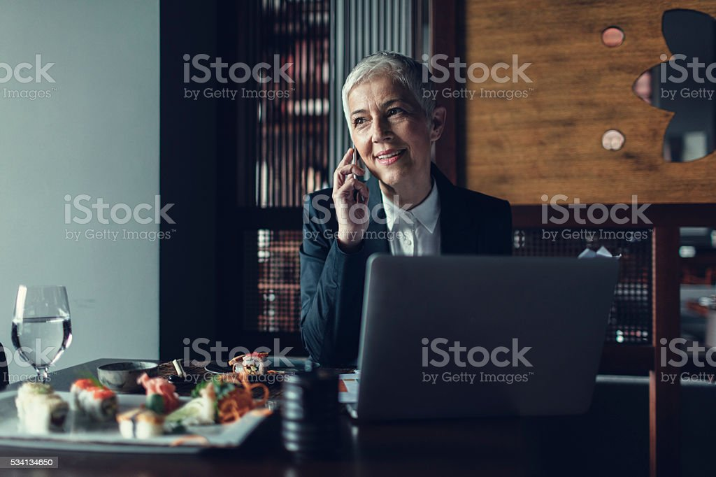 Mature Businesswoman Eating In A Restaurant And Working. stock photo