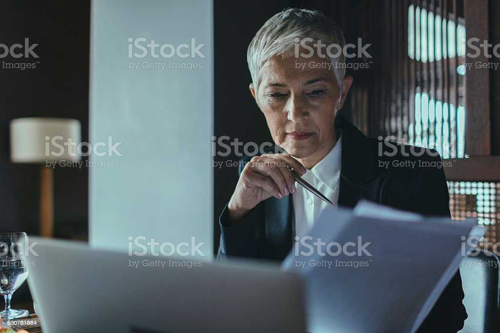 Mature Businesswoman Examining Documents. stock photo