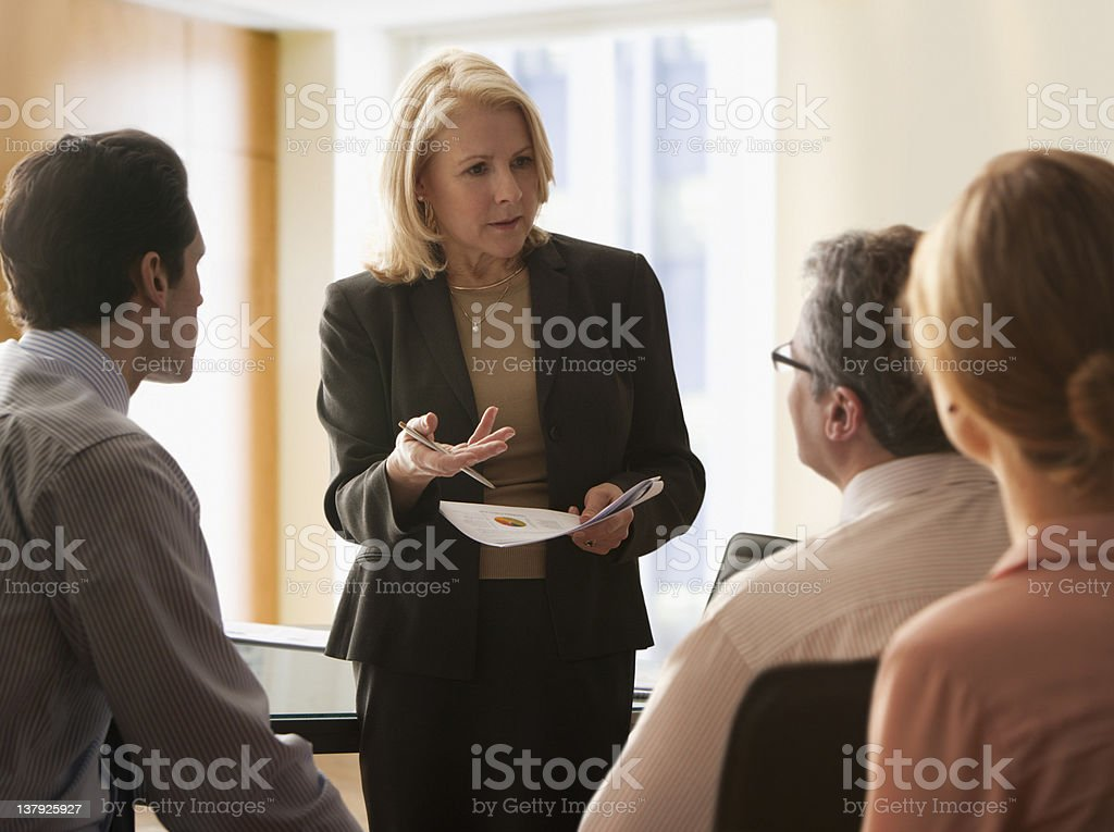 Mature businesswoman giving presentation to her colleagues stock photo