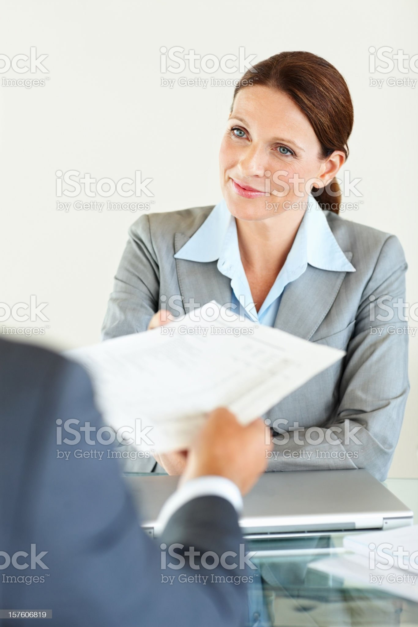 Mature businesswoman handing over document to male colleague royalty-free stock photo