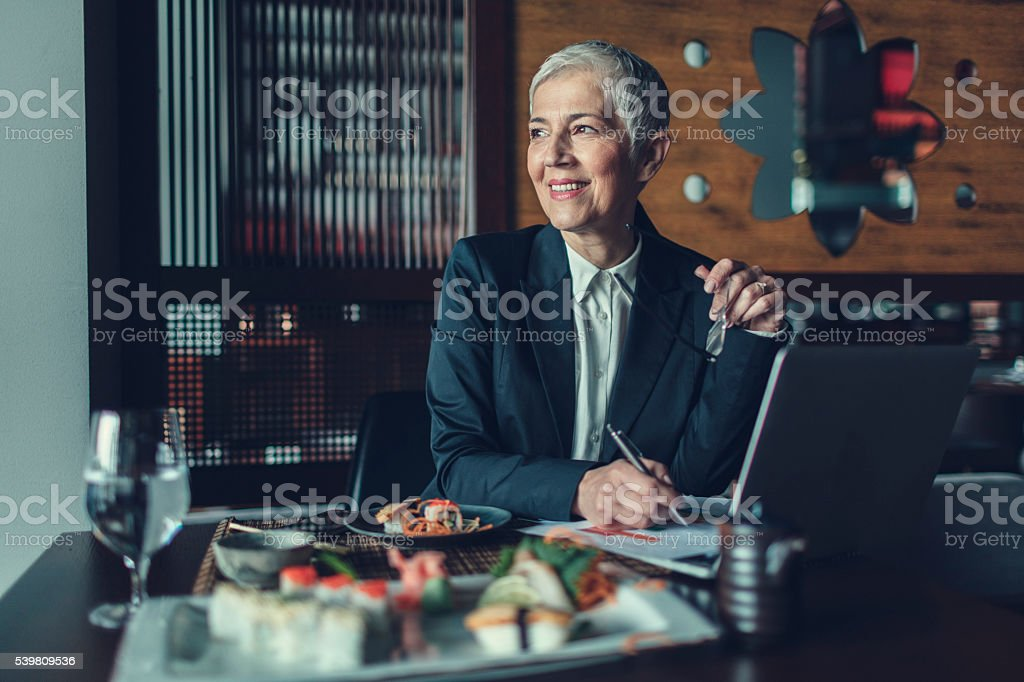 Mature Businesswoman Having Lunch And Talking On The Phone. stock photo