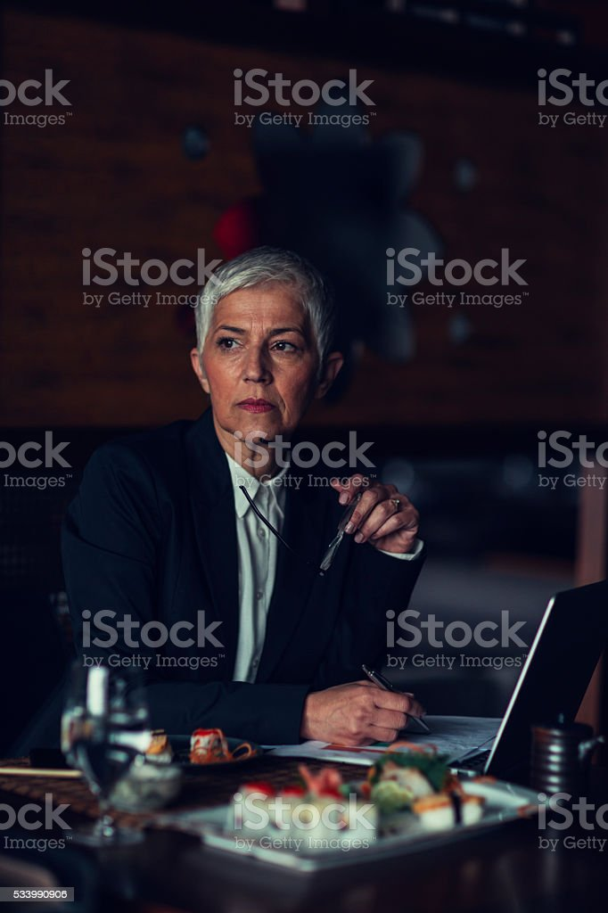 Mature Businesswoman Having Working Lunch. stock photo