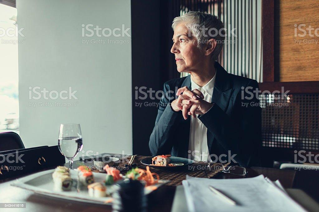 Mature Businesswoman Having Working Lunch stock photo