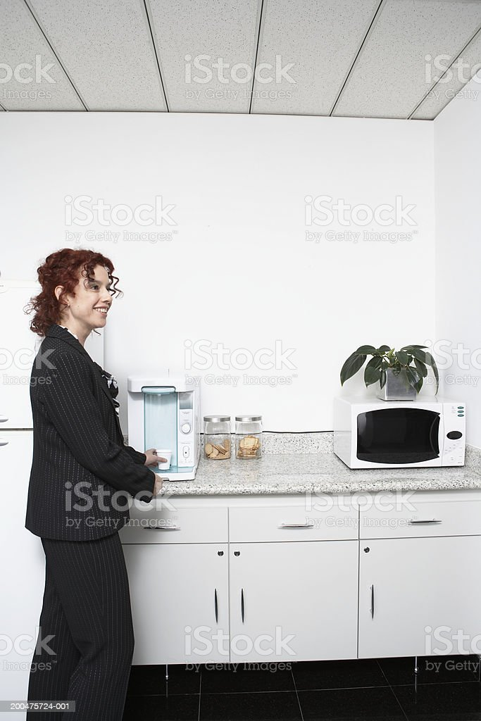 Mature businesswoman in office kitchen, side view stock photo
