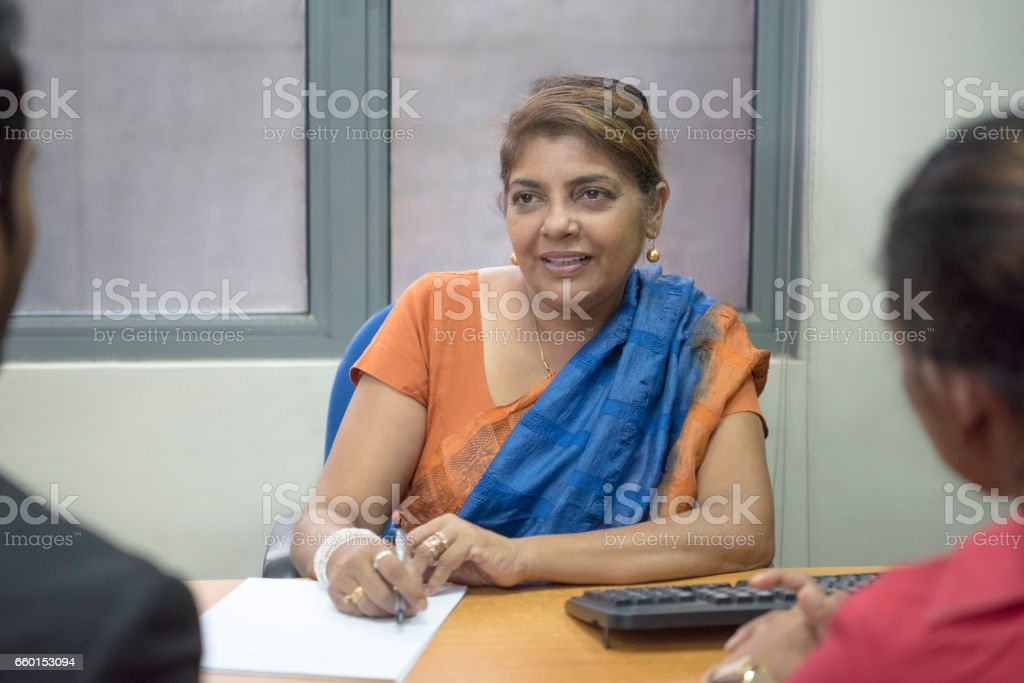 Mature businesswoman in sari discussing with colleagues stock photo