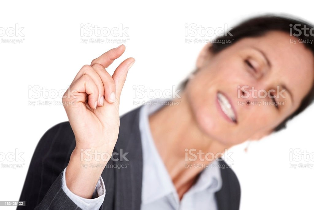 Mature businesswoman indicating a little bit royalty-free stock photo