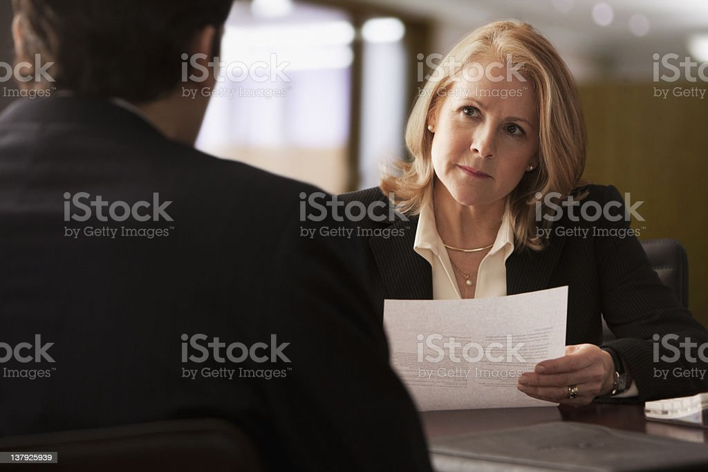 Mature businesswoman interviewing male candidate stock photo