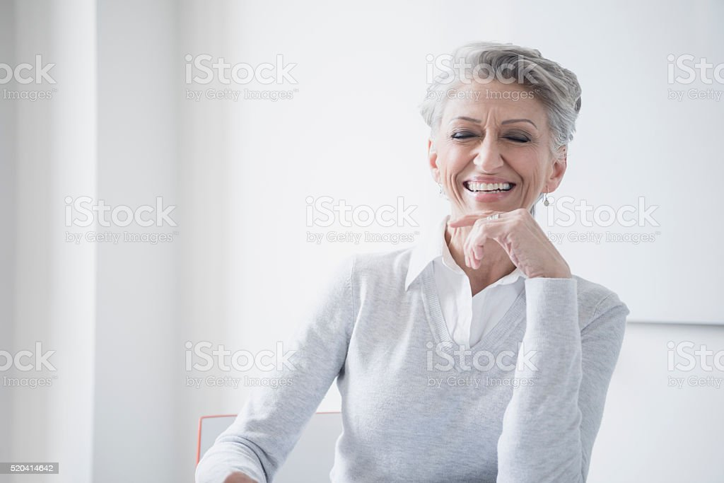 Mature businesswoman laughing with hand on chin stock photo