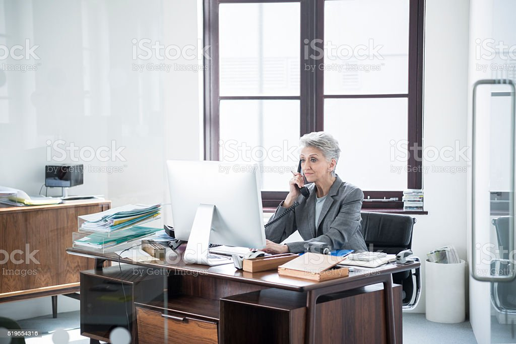 Mature businesswoman on the phone looking at computer stock photo