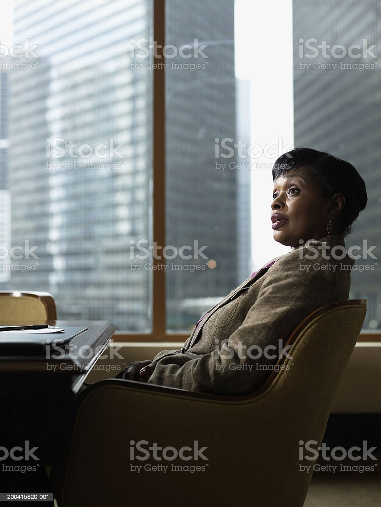 Mature businesswoman sitting at conference room table royalty-free stock photo