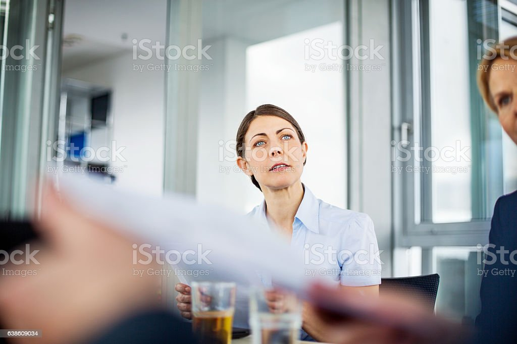 Mature businesswoman sitting attentively during meeting stock photo