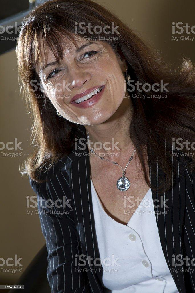mature businesswoman smiles royalty-free stock photo