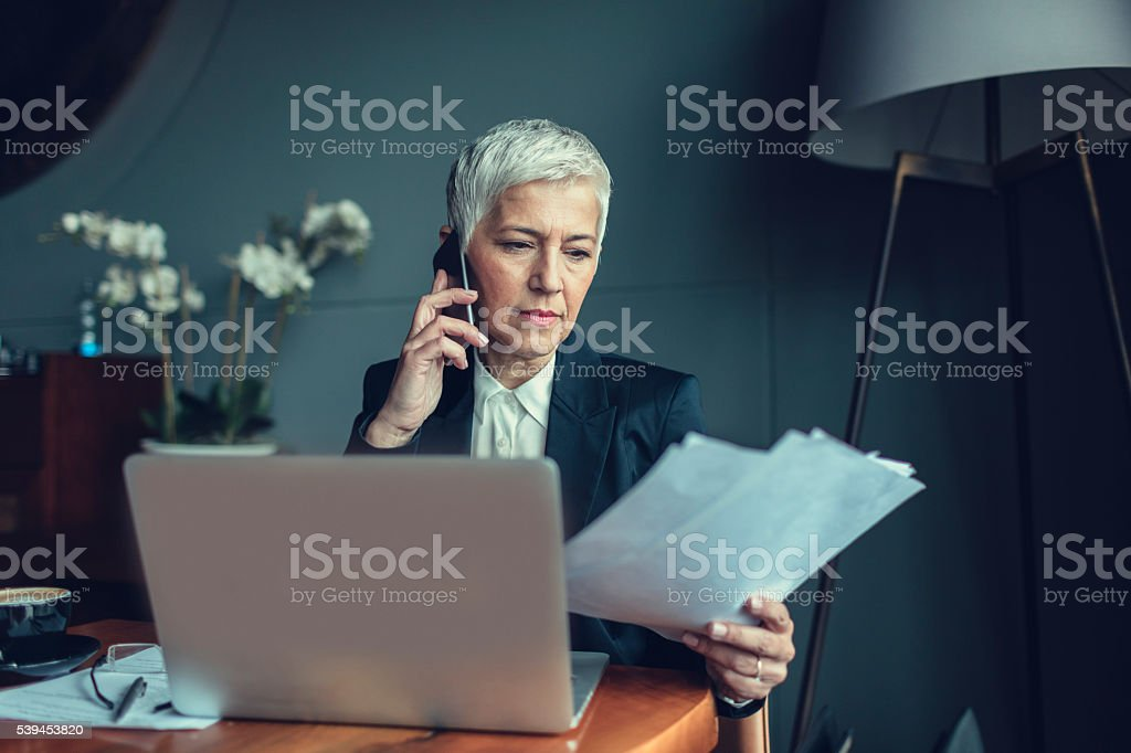 Mature Businesswoman Talking On The Phone And Examining Documents. stock photo