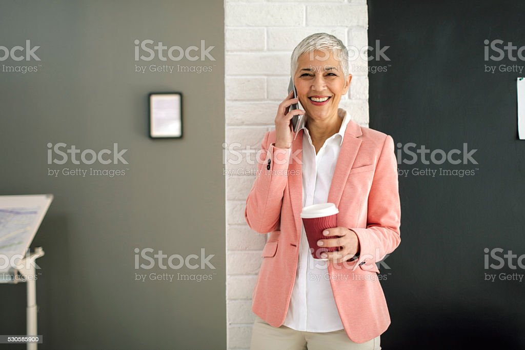 Mature Businesswoman Talking On The Phone In Her Office. stock photo