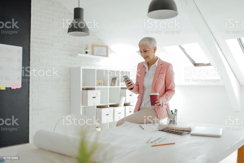 Mature Businesswoman Texting In Her Office. stock photo
