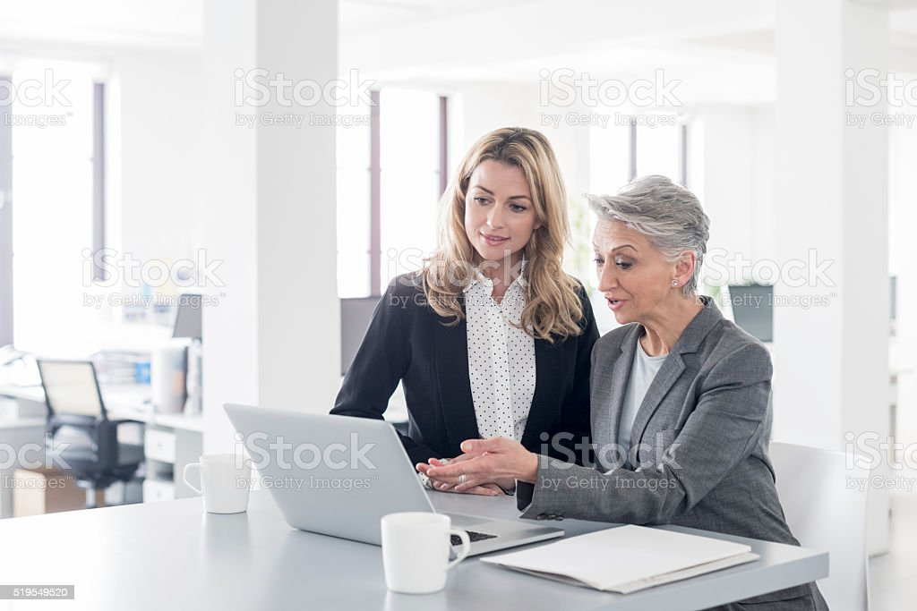 Mature businesswoman using latop with younger female colleague stock photo