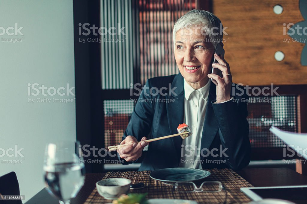 Mature Businesswoman Using Phone In Restaurant. stock photo