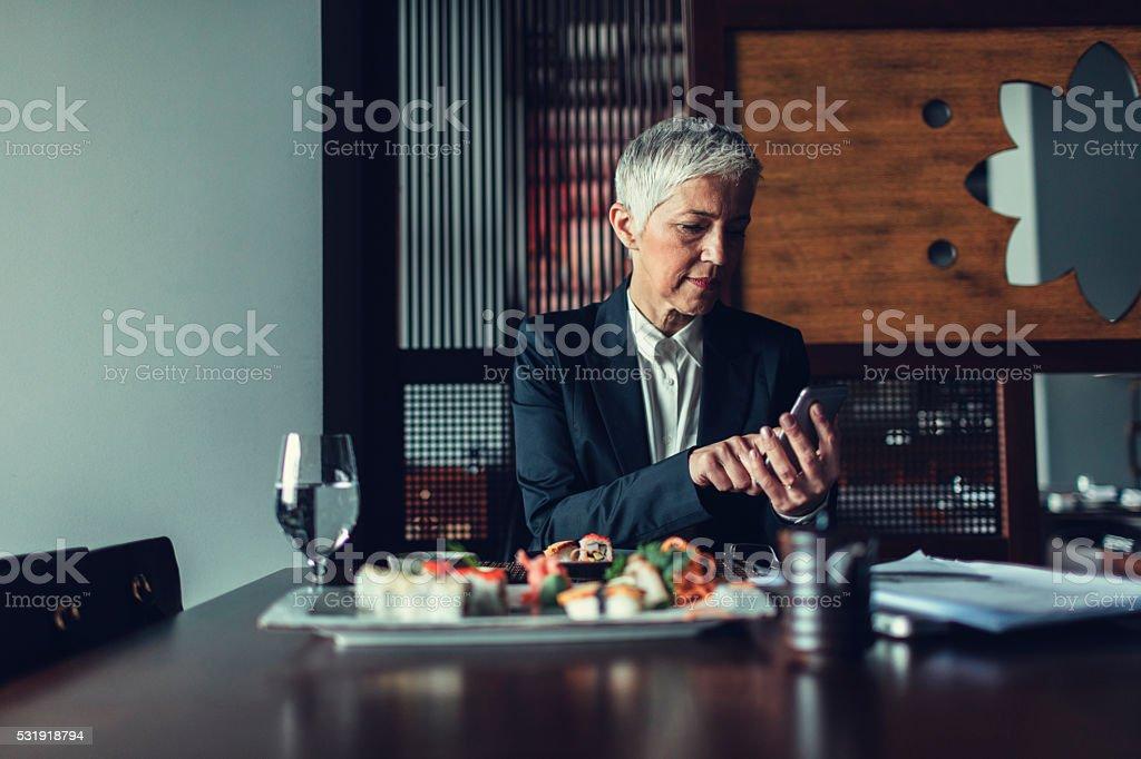Mature Businesswoman Using Smart Phone in restaurant. stock photo