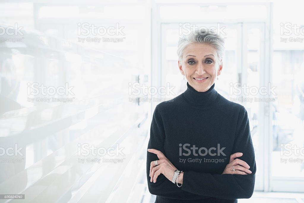 Mature businesswoman wearing black sweater in modern office stock photo