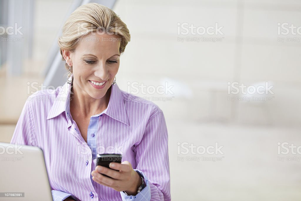 Mature businesswoman with laptop and mobile phone at office royalty-free stock photo