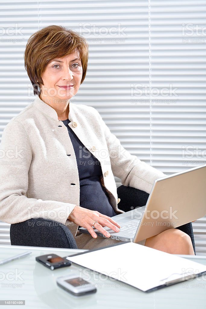 Mature businesswoman with laptop royalty-free stock photo