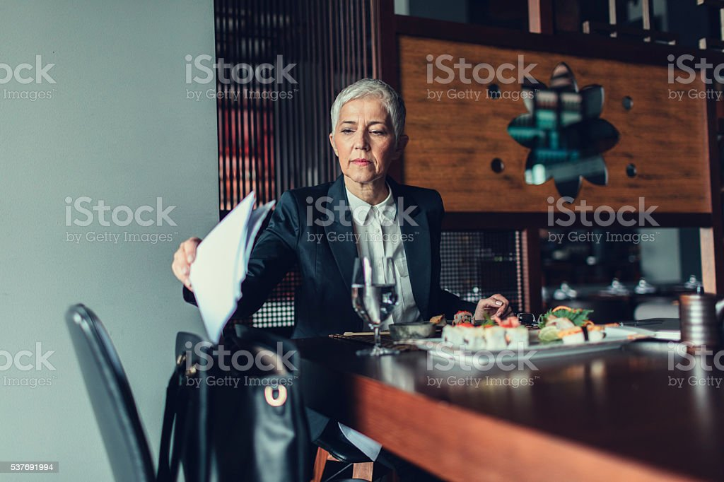 Mature Businesswoman Working and Having Lunch In Restaurant. stock photo