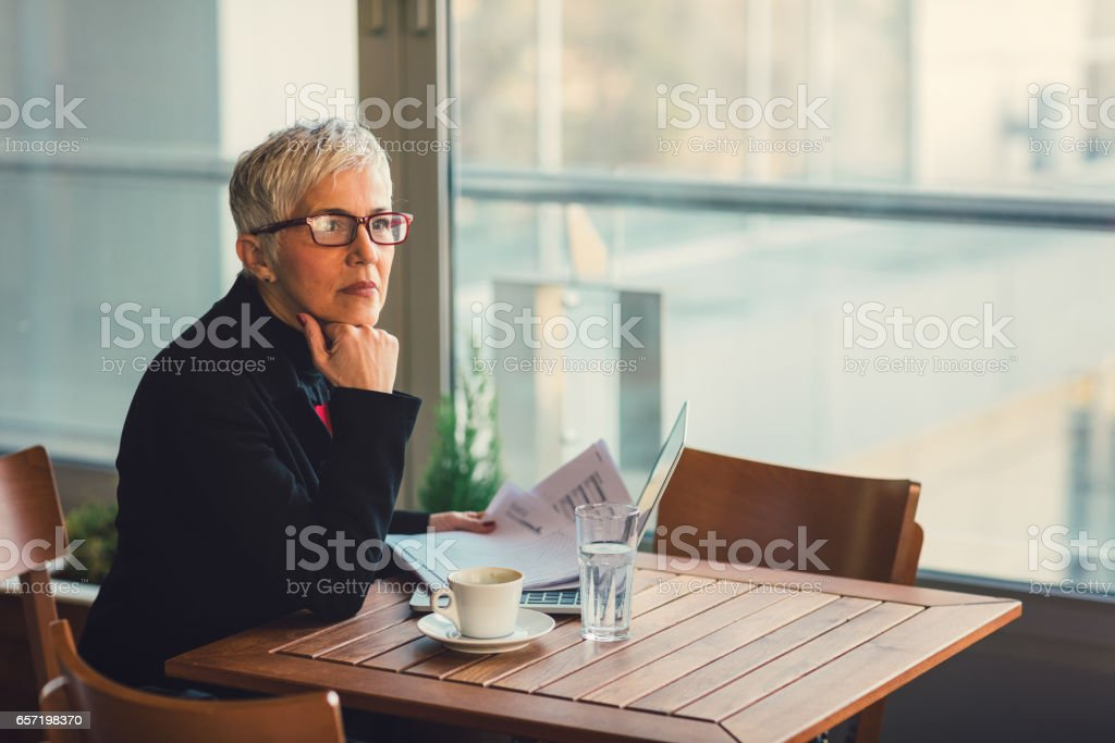 Mature businesswoman working in cafe stock photo